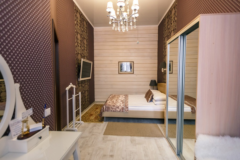 Bedroom with wooden wall of Suite room Abazhur Hotel Tomsk